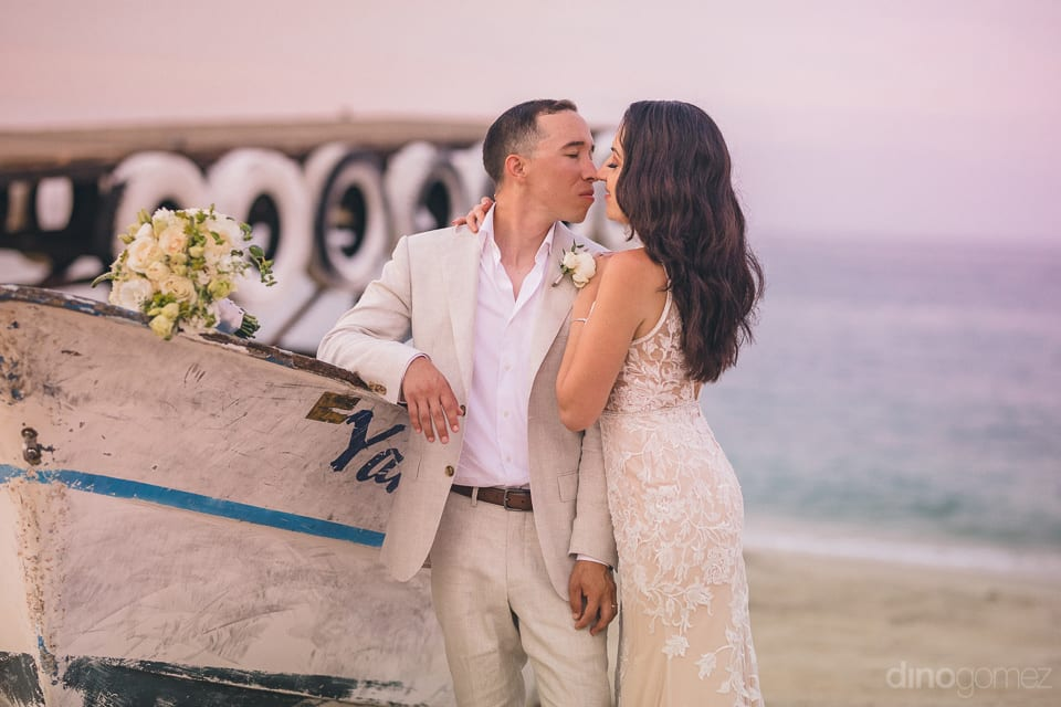 Lovely Couple Is Standing Infront Of An Abondant Boat At The Beach And Giving A Romantic Pose For The Camera- Christina & Steve