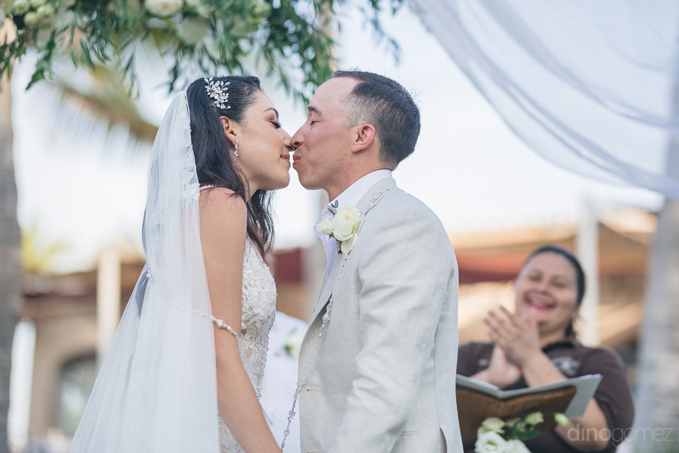Charismatic couple is about to kiss each other during the wedding ceremony in the presence of wedding guests- Christina & Steve