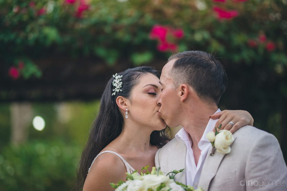 Lovely couple is kissing each other and facing the camera for the moment to be captured by it- Christina & Steve