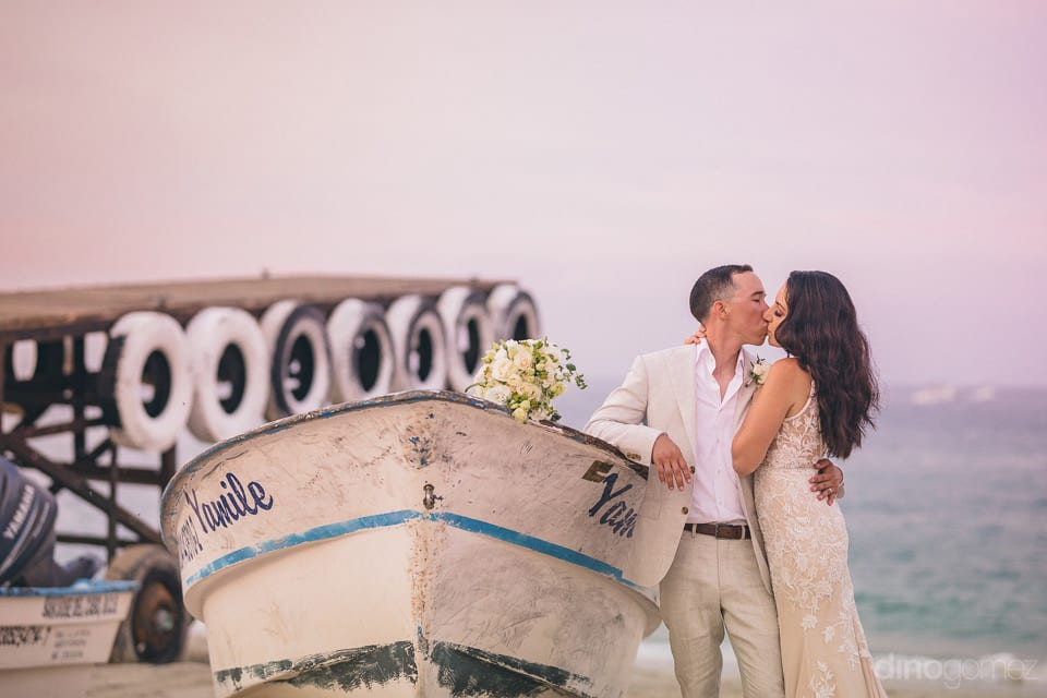 The Couple Is Standing Infront Of A Boat At The Sea Shore And Are Romantically Kissing Each Other To Give A Striking Pose- Christina & Steve