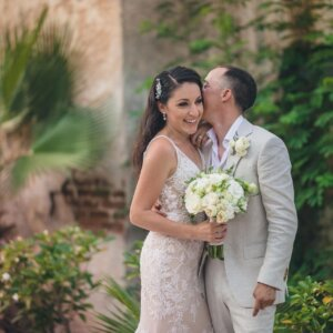 The gorgeous bride is looking charismatic while getting kissed by the groom on her cheeks standing in the lush green garden- Christina & Steve