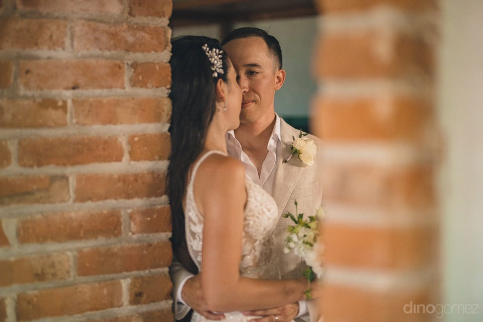 Picture captures the lovely pose of the newly married couple from behind the brick walls- Christina & Steve