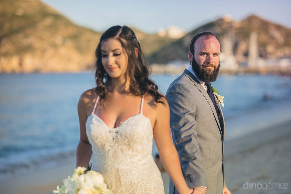 The couple is posing for the camera standing infront of the beautiful sea. The bride is facing the camera and the groom is giving a side pose- Nicole & Ryan