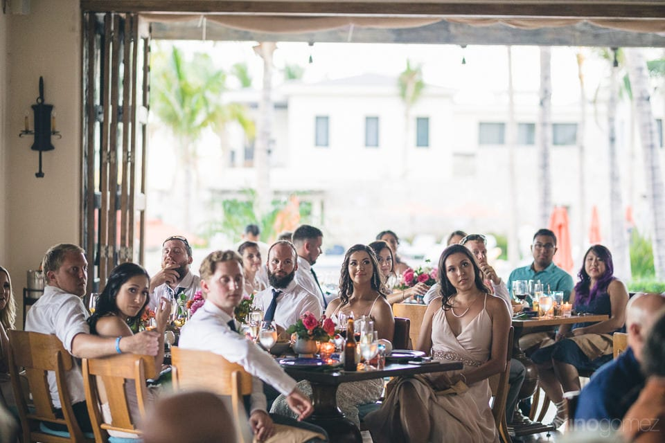 The picture captures the newly married couple sitting along with other guests on the chairs at the reception venue- Nicole & Ryan