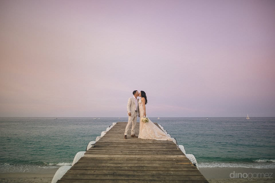Amazing Couple Is Kissing Each Other Standing On A Wooden Bridge And Is Giving An Astonishing Pose For The Camera- Christina & Steve