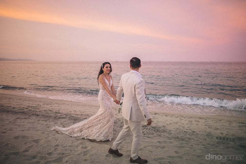 The lovely couple is holding each others hands and is walking at the beach side with big waves at the sea- Christina & Steve