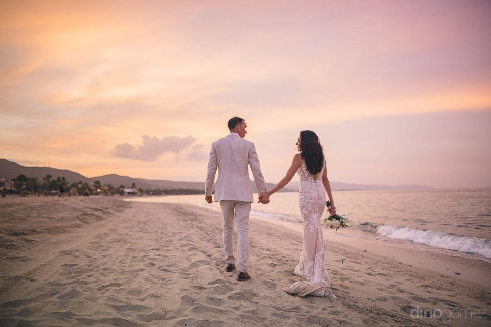 Picture Captures The Back View Of The Couple Walking At The Beach Side Holding Each Others Hands At The Sunset- Christina & Steve