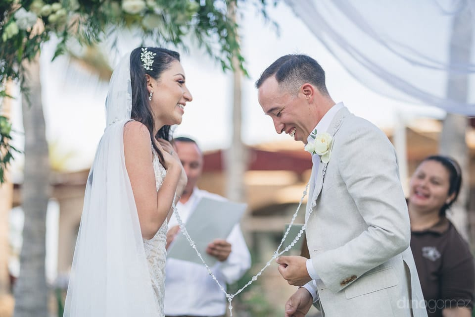 Gorgeous couple is wearing a holy chain and laughing together in the presence of the guests- Christina & Steve