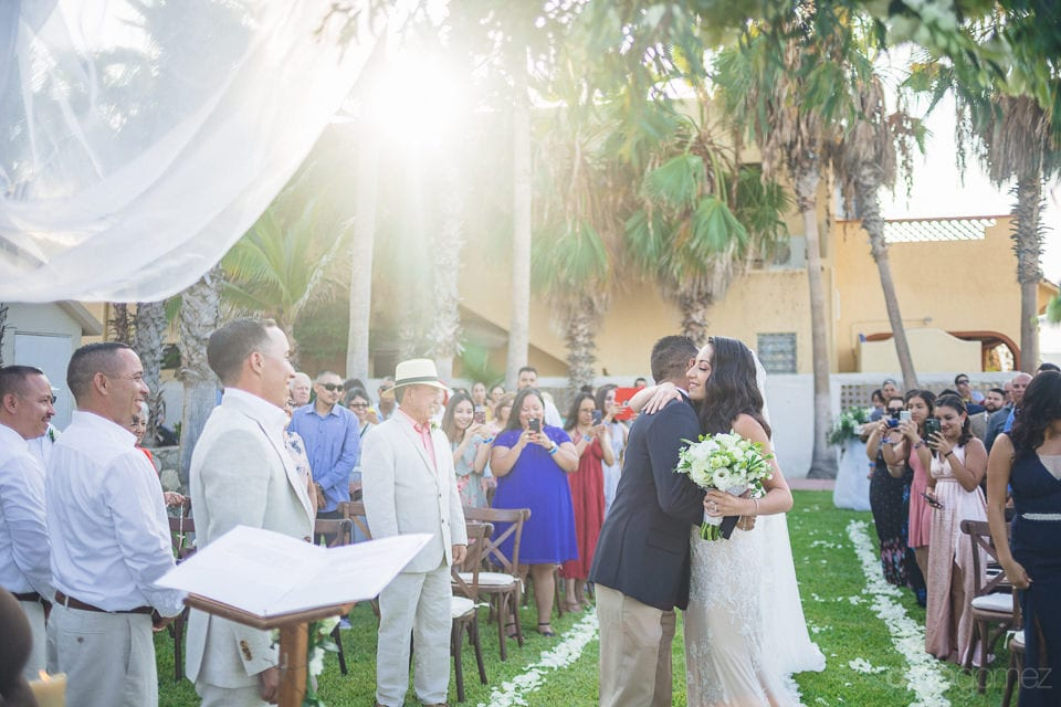 Gorgeous bride is hugging a gentleman before holding the hands of the groom standing at the wedding stage- Christina & Steve