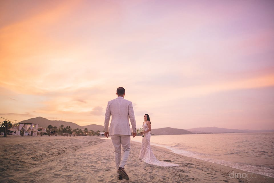 Lovely bride and groom are standing on the golden sand and the bride is turning back and looking at the groom to give a striking pose for the camera- Christina & Steve