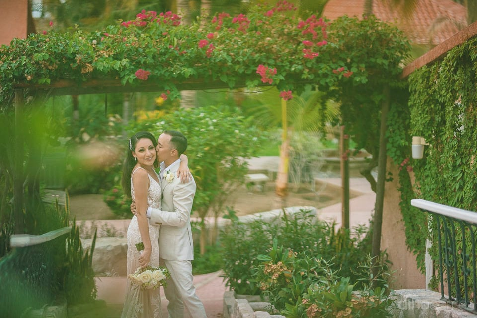 Newly Married Couple Is Standing Under A Beautiful Gate Made Out Of Flowers At The Beautiful Garden- Christina & Steve