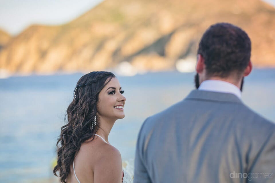 The picture focuses on the lovely bride while she is walking with the groom at the sea side- Nicole & Ryan