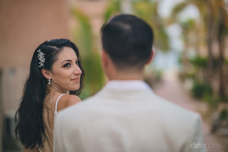 Gorgeous bride is looking at the groom and smiling while he stands beside her- Christina & Steve