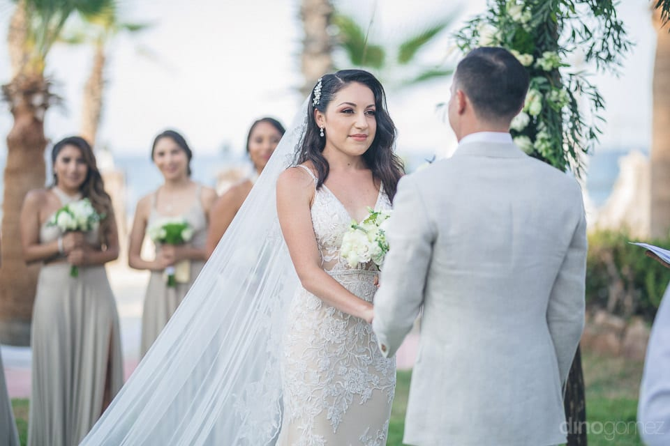 Picture captures the beautiful bride dressed in white gown holding hands of the groom during the wedding ceremonies- Christina & Steve