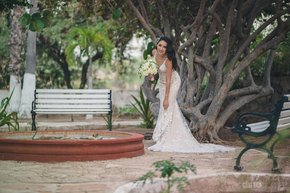 Lovely bride is setting her wedding gown standing next to a big tree and is looking at the camera- Christina & Steve