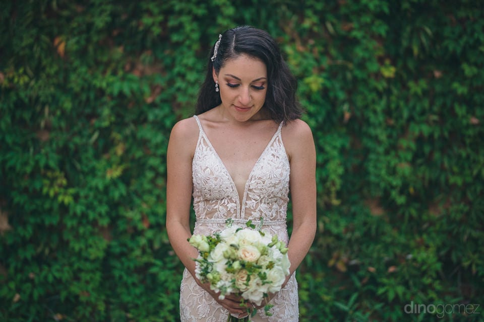 The bride is looking angelic in her wedding gown and holding her wedding bouquet in hands- Christina & Steve