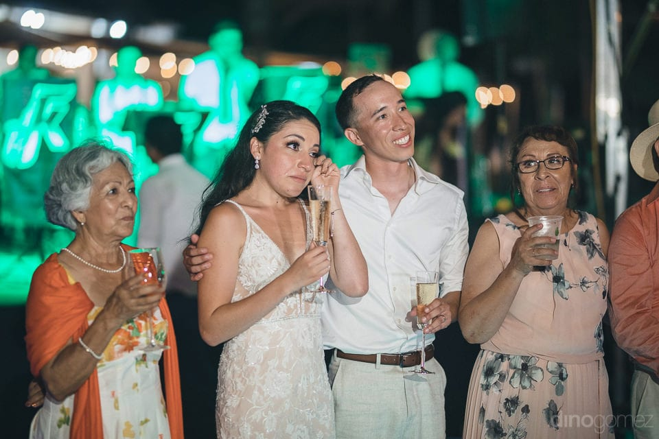 The Bride Is Standing Next To The Groom And With Her Family Members And Is Wiping Her Tears During The Evening Party- Christina & Steve