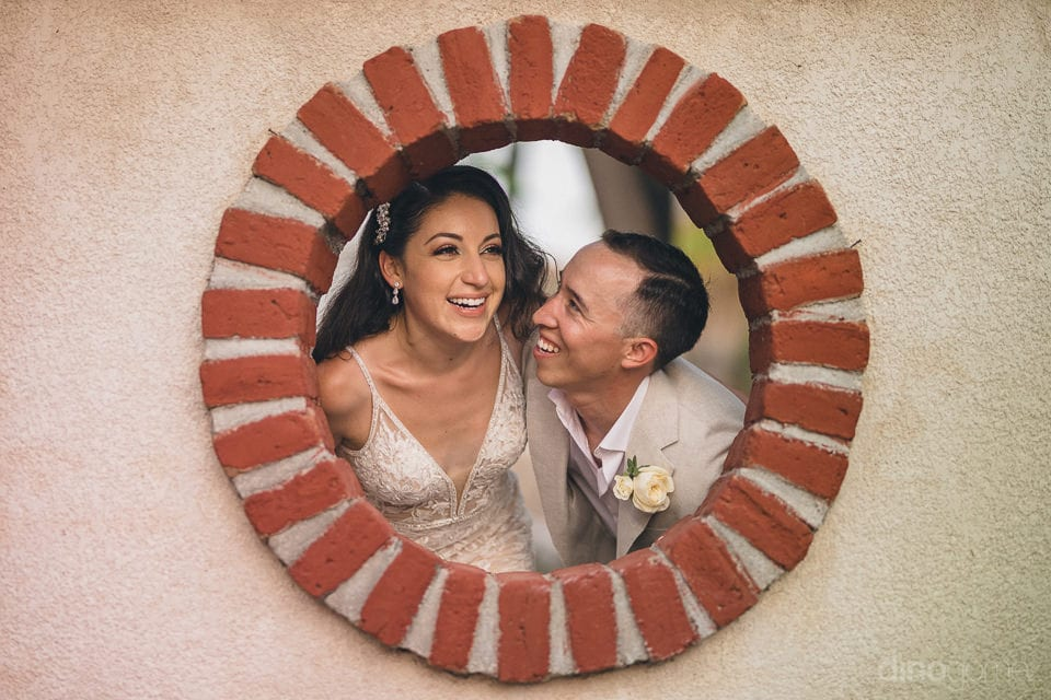 Newly Married Couple Is Peeping Through A Hole In The Wall Made Out Of Bricks For The Camera- Christina & Steve