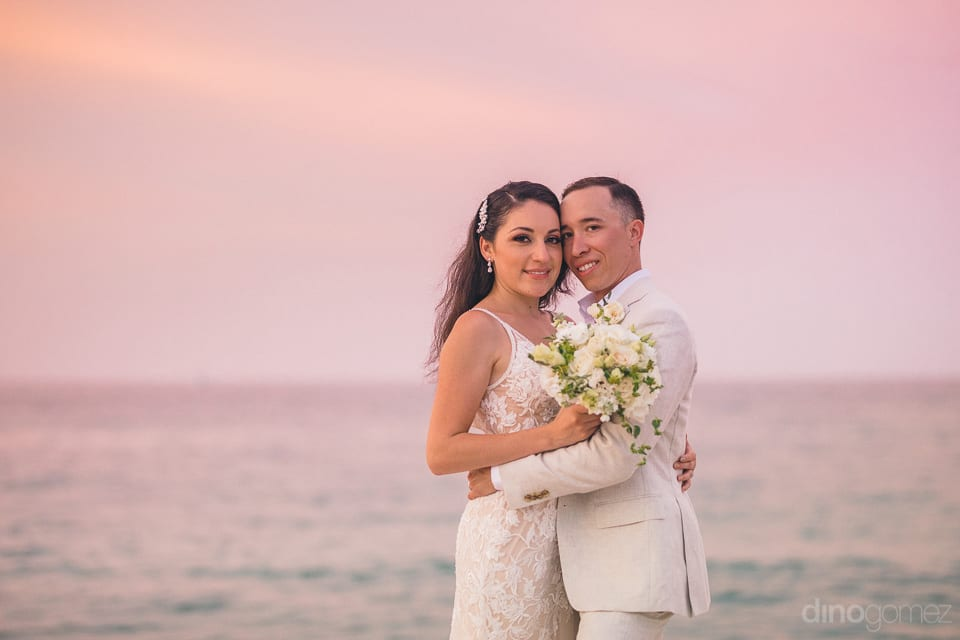 Lovely Couple Is Hugging Each Other During The Sunset While Standing Next To A Beach- Christina & Steve