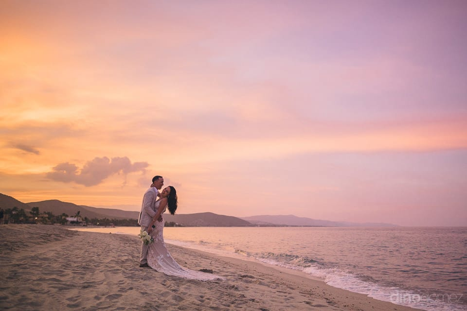 The lovely newly married couple is laughing loudly standing on the golden sand to pose for the camera- Christina & Steve