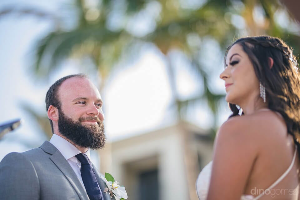 A lovely moment of the groom smiling at bride while the bride is looking away from the camera is captured in the camera- Nicole & Ryan	A romatic moment of the groom looking at the bride is captured in the picture. The groom is smiling while looking at her