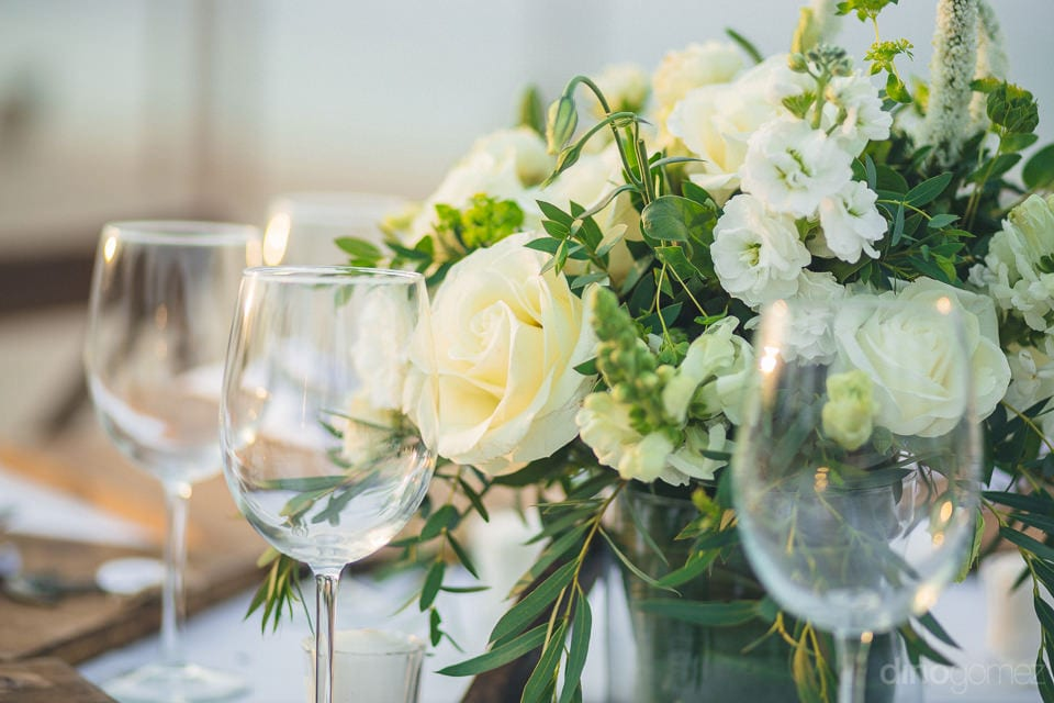 Picture Captures The White Roses And Green Leaves Placed On The Vase On The Dinning Table- Christina & Steve