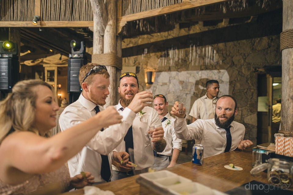 The groom and a few other guests are raising a toast to the newly married couple standing at the bar during the reception party- Nicole & Ryan
