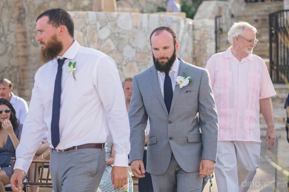 Handsome groom is dressed in his grey suit and is walking towards the wedding venue- Nicole & Ryan