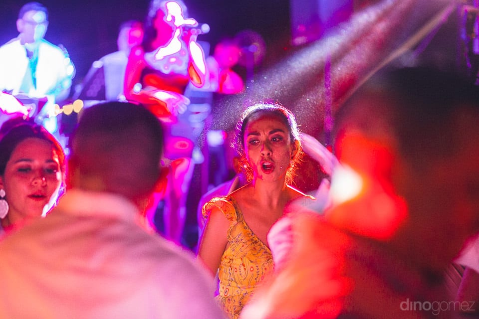 A smart lady is dancing on the dance floor and is dancing under the bright lights at the reception party- Christina & Steve