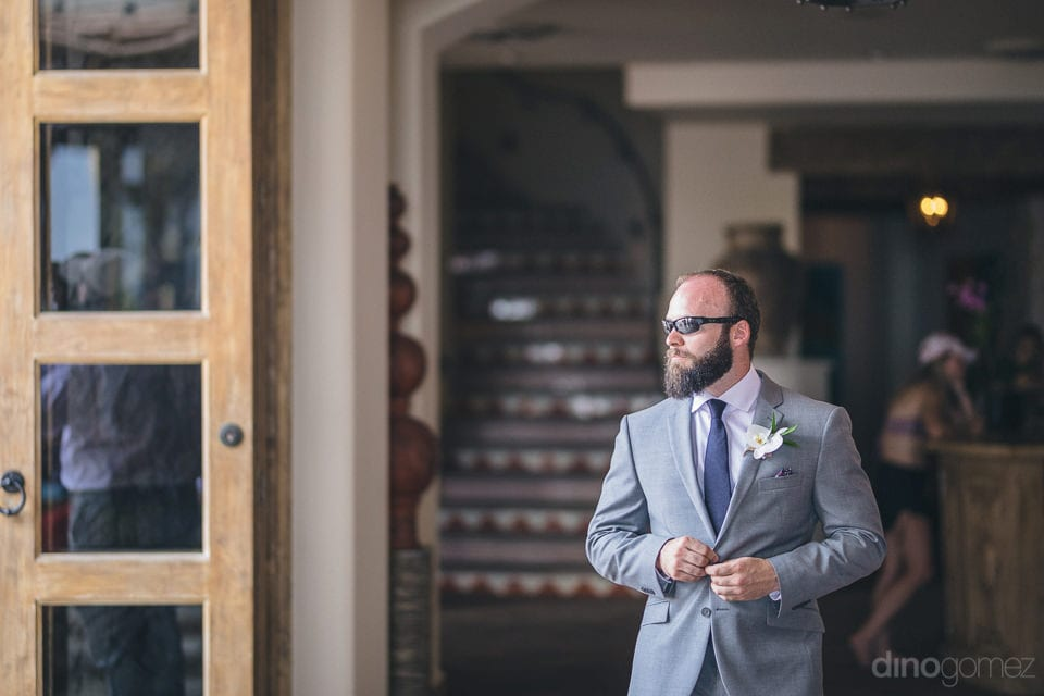 Handsome groom is posing in his grey wedding suit and black sunglasses for the camera- Nicole & Ryan