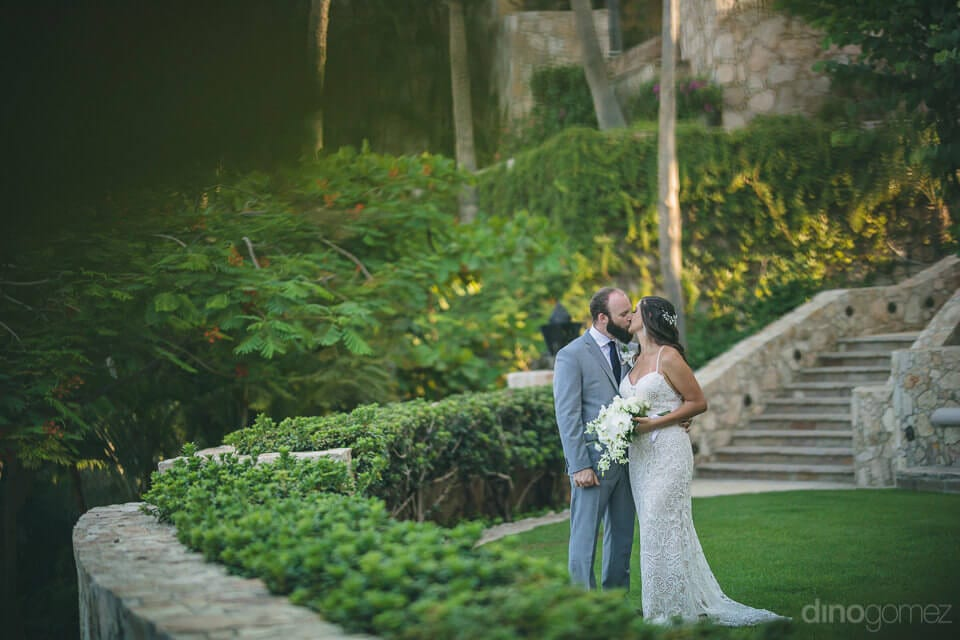 Newly married couple is kissing each other standing in the beautiful lush green garden- Nicole & Ryan