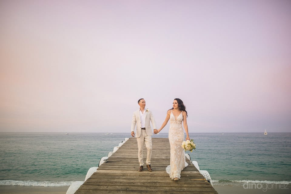 The bride and groom are walking on the wooden bridge over the calm sea after the completion of wedding ceremonies- Christina & Steve