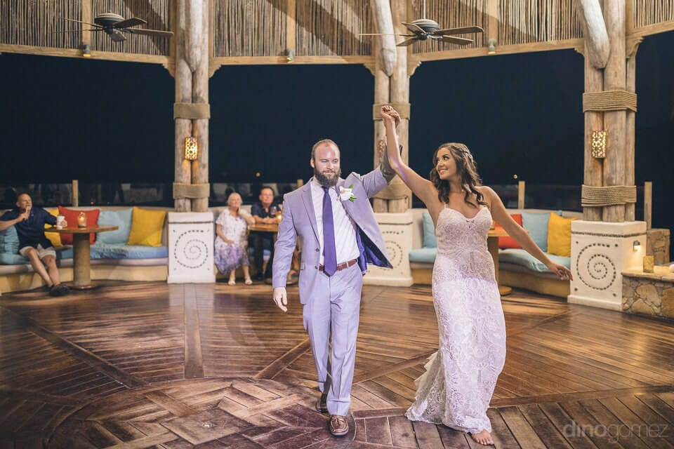 Lovely bride and handsome groom are dancing alone on the dance floor with their hands up in the air at the reception party- Nicole & Ryan