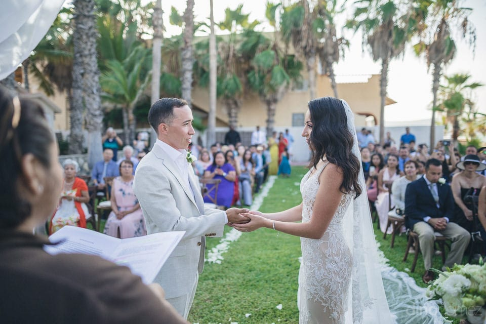 The couple is holding each others hands and smiling at each other while a lady is reading out something from a piece of paper during the wedding ceremonies- Christina & Steve