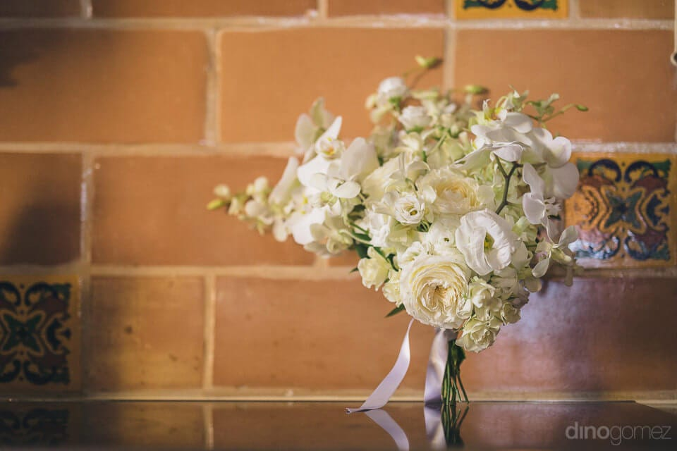 A beautiful bouquet of white roses is placed infront of the wall made up of tiles- Nicole & Ryan	A lovely bouquet of white roses is captured in the picture placed infront of the lovely brown wall made up of tiles- destination wedding of the gorgeous coupl
