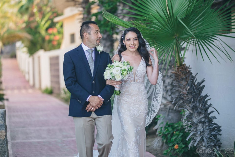The Bride Is Looking Gorgeous In Her White Gown And Is Walking Towards The Wedding Stage Holding A Bouquet In Her Hands- Christina & Steve