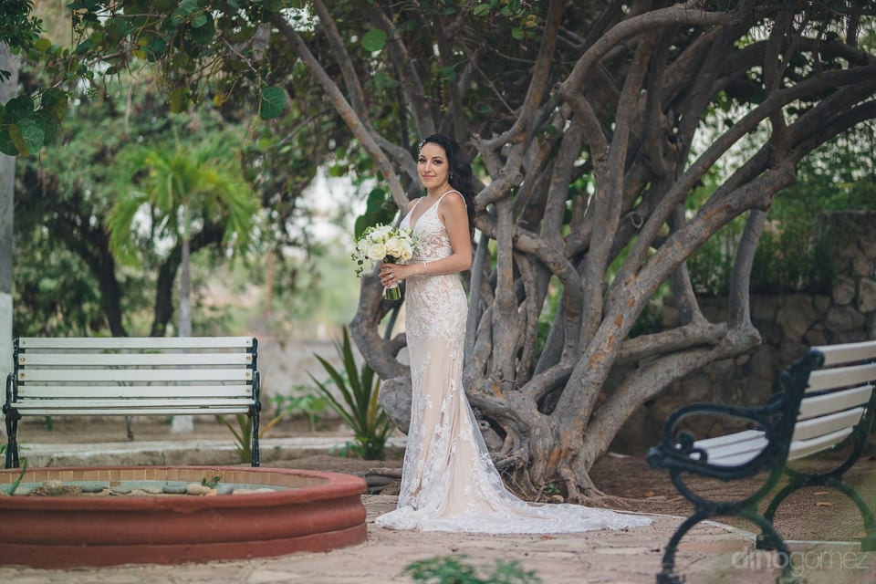 The Bride Is Holding Her Wedding Bouquet And Is Posing Beautifully Infront Of A Big Tree For The Camera- Christina & Steve