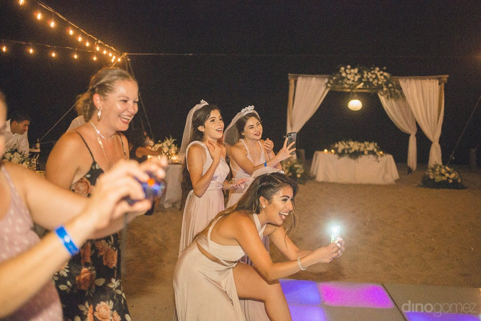 Lovely Young Ladies Are Holding Their Phones And Making Video Of Something At The Reception Party Of The Couple- Christina & Steve