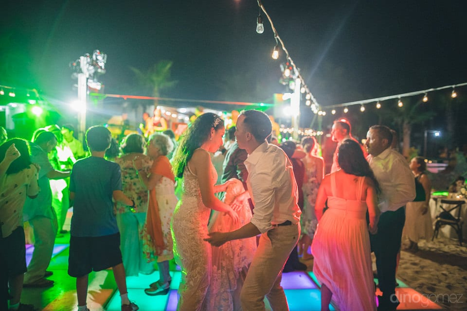 All the wedding guests are dancing on the dance floor along with the newly married couple under the colorful LED lights- Christina & Steve