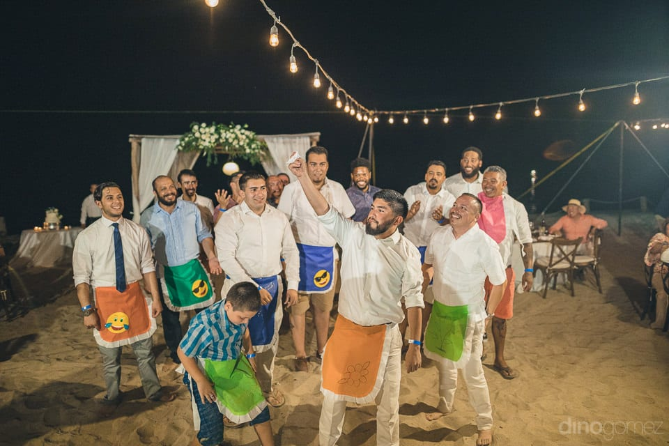 All The Handsome Men Are Standing On The Golden Sand And Are Enjoying The Evening Reception Party Games To The Fullest- Christina & Steve