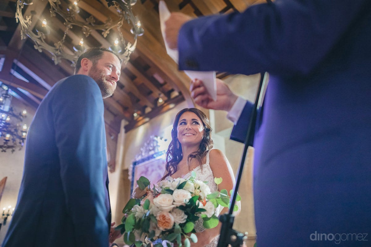 The lovely couple is happily looking at the priest reading out a piece of paper during the wedding ceremony standing under beautiful wooden roof-  Kathleen & Kevin