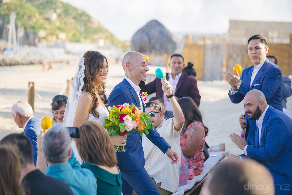 Pretty couple is walking on the isle wearing broad smiles and holding each others hands at the beachside- Nikki and David