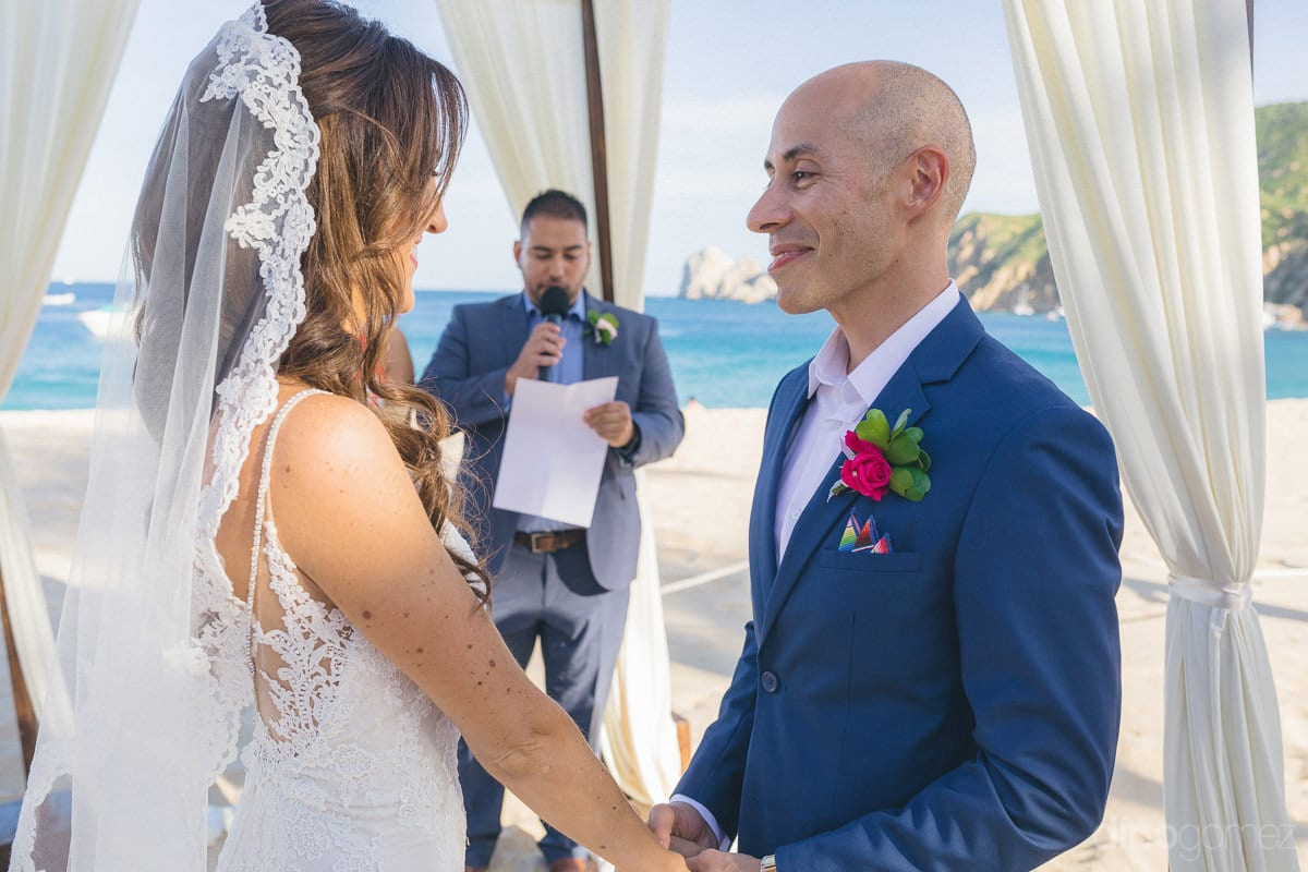 Gorgeous couple is standing on the wedding stage and smiling adorably at each other during the wedding ceremony- Nikki and David