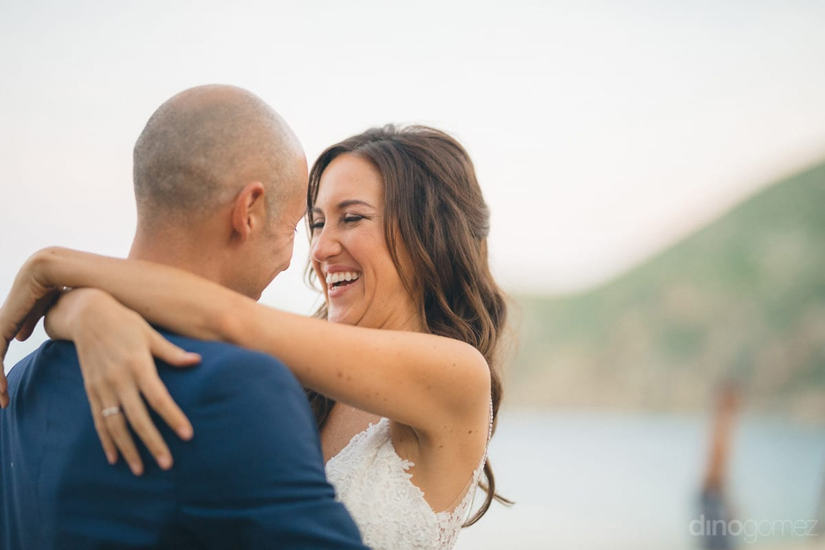 Pretty bride has her arms around the shoulders of her groom and is smiling broadly looking deep into his eyes- Nikki and David