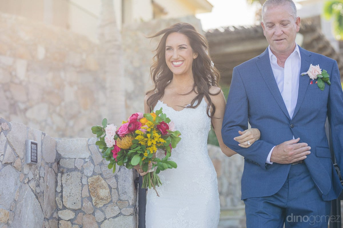 A superb picture of the bried dressed in amazing white wedding gown with flowing hair while walking towards the wedding venus is captured- Nikki and David