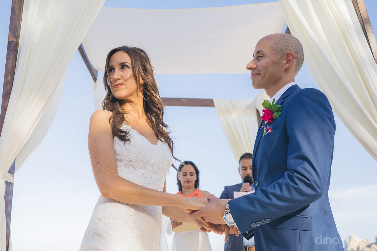An adorable picture of the groom looking at bride while holding her hands during the wedding ceremony is taken- Nikki and David