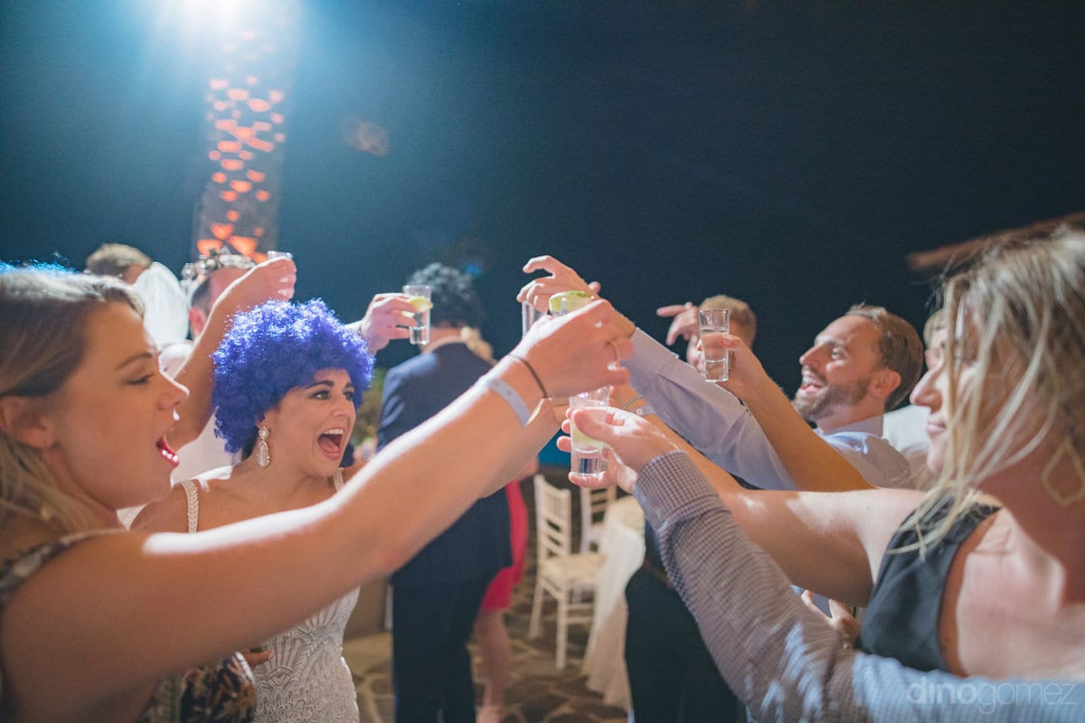 Gorgeous Bride Is Wearing A Blue Head Mask And Is Happily Raising A Toast At The Reception Party At The Beach Side- Kathleen & Kevin