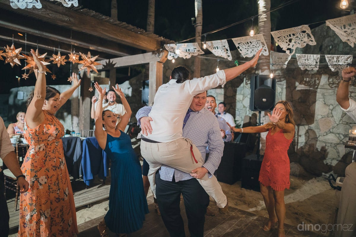Wedding guests are having extreme fun while dancing at the beachside evening reception party of the couple- Nikki and David