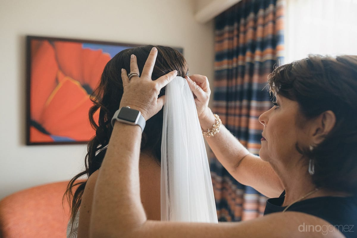 The beautiful bride is getting her head veil fixed with the help of a gentle lady standing inside the beach room for the wedding- Kathleen & Kevin