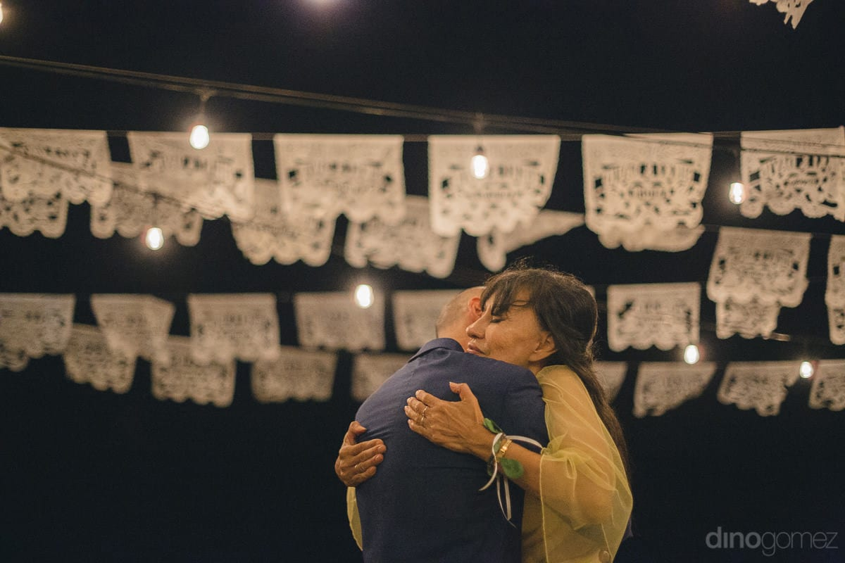 A young man and a beautiful lady are emotionally hugging each other at the reception party under the glowing LED lights- Nikki and David